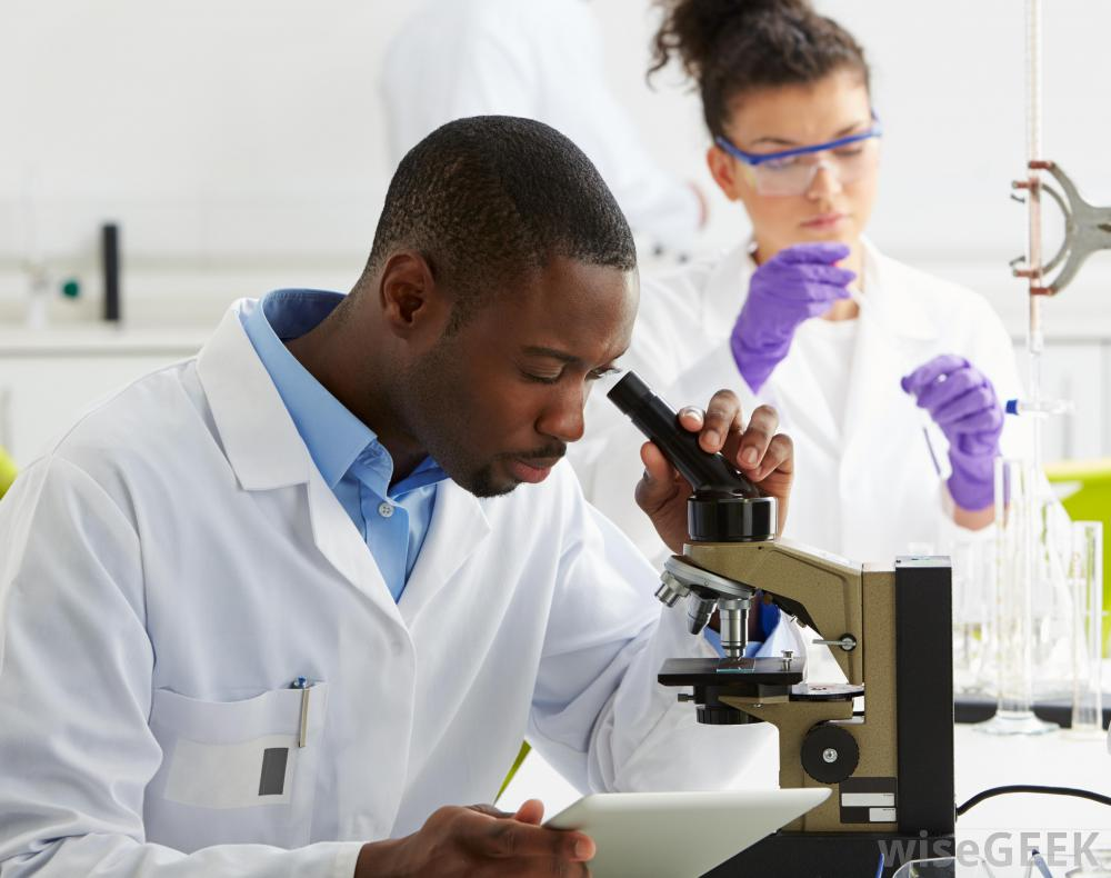 african-american-male-in-lab-coat-looking-into-microscope-near-woman